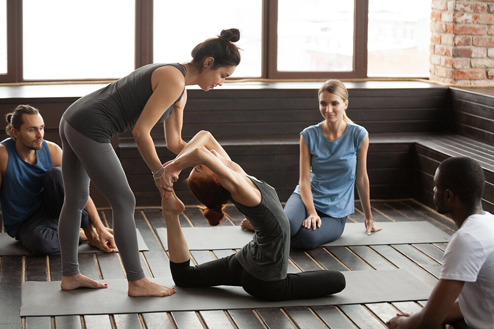 https://ayukshema.com/wp-content/uploads/2021/01/female-yoga-instructor-helping-woman-doing-exercise-group-tra-1000x667.jpg